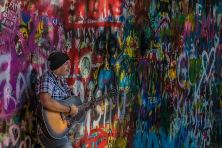 Street Busker performing Beatles songs in front of John Lennon Wall on Kampa Island. Busking is legal form of earning money on Praha Streets. 스톡 콘텐츠 - 138479164