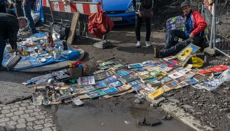 Krakow, Poland - September 21, 2019: Man sells a lot of books on the edge of a puddle of water at the Krakow street flea market. Editoriali
