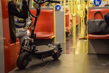 Vienna, Austria - September , 16, 2019: People, a motorized scooter and dogs are passengers inside a Vienna subway car