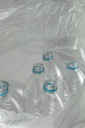 Inside an open transparent plastic bag with several empty bottles of liter and a half mineral water, without caps, just with the blue sealing ring.  Reuse, Eco-Friendly, Environment, Conservation, Sustainable and Resources concept. Standard-Bild