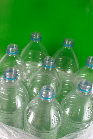 Verticam image of a pack of 8 empty and recyclable plastic water bottles, with no caps, blue seal, in a plastic bag, on a colored  green background. Reuse, Eco-Friendly, Environment concept. Banque d'images