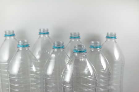 Pack of standing Bottles of a liter and a half of empty mineral water without caps just with the sealing ring on a white background. Reuse, Eco-Friendly, Environment, Conservation, Sustainable and Resources concept.