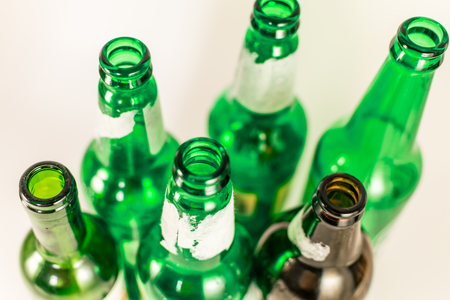 Top view of a pack of empty green and brown wine and beer glass bottles, with ripped labels on a white background. Reuse, acoholism, recycle and party concept. Warm tones.