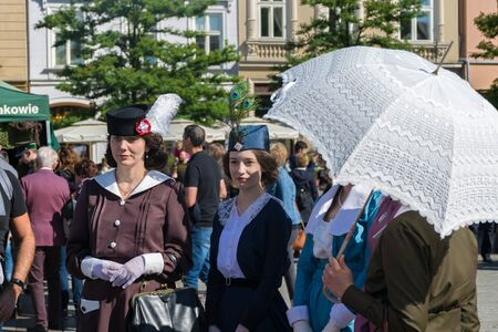 Krakow, Poland - September 23, 2018:   Stylish young women dressed in World War I period clothing walk among tourists at krakows main square