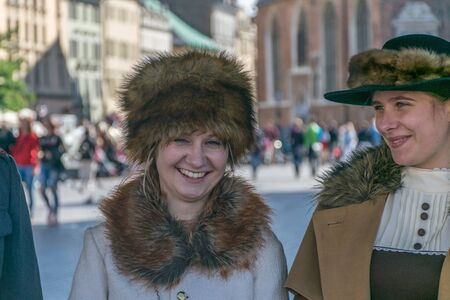 Krakow, Poland - September 23, 2018:   Stylish Pretty young woman dressed in World War I period clothing smiling among tourists at krakows main square