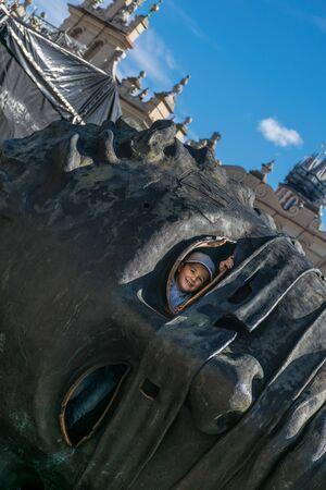 Krakow, Poland - September 23, 2018:  smiling kid looking through the eye hole of the Head sculpture Eros Bendato on Market Square,made by polish artist Igor Mitoraj in Krakow