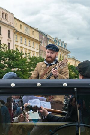 Krakow, Poland - September 23, 2018:  Musician dressed as peasant singing and playing guitar with a band on top of an antique pickup truck at the main square of Krakow Banque d'images - 138479295