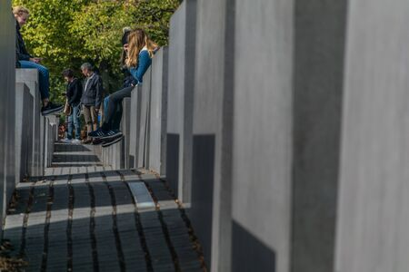 Berlin, Germany - September 23, 2018: Horizontal and perspective view of people sitting at the Memorial to the Murdered Jews of Europe, in Berlin, Germany, a Peter Eisenman project.