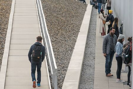 BERLIN, GERMANY - SEPTEMBER 26, 2018: Contrasting picture of a person alone going up a ramp and people standing in a corridor at a temporary exhibition in the Topography of Terror history museum
