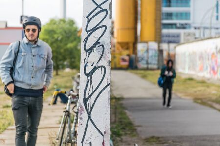 BERLIN, GERMANY - September 26, 2018: Artistic contraposition with a focus in the graffiti of a wall that separates two sides of the East Side Gallery, the Spree river banks and the Berlin Wall