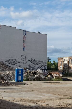 BERLIN, GERMANY - July 28, 2018: Perspective of an angel painting in white wall behind a lot of construction debris, a dumpster and a blue chemical toilet near an old building in a wasteland in Berlin