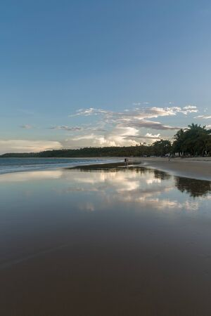Amazing sunset at a beach bay with mountains covered by natural vegetation near the skyline and the ocean water reflecting the beautiful and gradient color palette of the sky at Trancoso, Porto Seguro