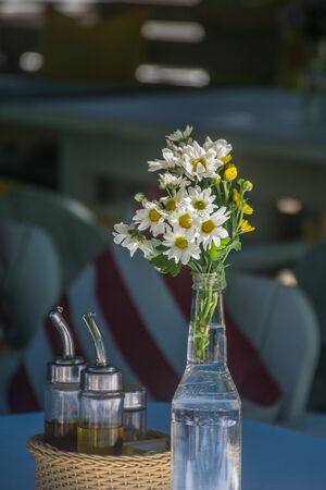Transparent bottle filled with water carries a bouquet of daisies, a wood basket has some recipients with condiments and seasonings inside of it on the left side of the bottle, it is a restaurant Imagens