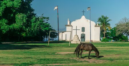 Horse is eating grass in front of Quadrado Church, there is a cross, a goal post and to tall flags between the temple and the animal, a forest on the left and a palm tree on the right in Trancoso