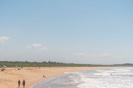 A person swims in the atlantic ocean, a couple walks, some people are chilling under their beach umbrella, native vegetation is behind the strand at Paulo Cezar Vinha park, in Setiba, Espirito Santo