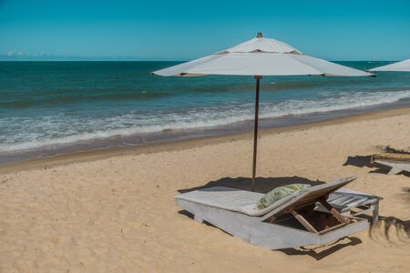 A relaxing setting near the sea with a reclining comfortable chair and a white parasol in a resort hotel at a paradisiac tropical beach perfect for summer vacations. Imagens