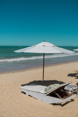 Tropical scenic view of white recliner chairs under a white parasol of a resort and near the green ocean, a perfect place for an afternoon nap during a summer trip at Trancoso, Porto Seguro, Bahia