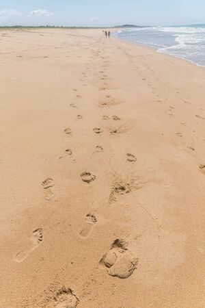 A long track of footprints, two couples, one is so far ahead they can bearly be seen, the atlantic sea is on their right side with its foamy waves at Paulo Cezar Vinha park, in Setiba, Espirito Santo