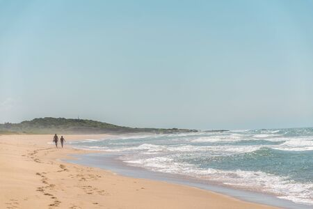 Couple walks towards a hill, footprints, no clouds, the ocean is full of foam due to the waves, they are near to the end of the beach at Paulo Cezar Vinha park, in Setiba, Espirito Santo