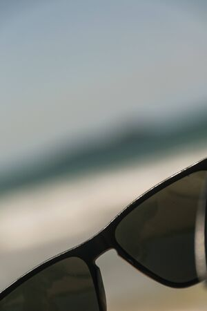 In a blury background, a black sunglasses stands out, its lenses are also black and they are translucid, the glasses cannot be seem as a whole, only its central part where it fits the nose