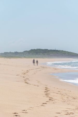 Trails of footprints in the sand reaches a couple who face a hill covered with vegetation, on their side is the atlantic and its foam at Paulo Cezar Vinha park, in Setiba, Espirito Santo