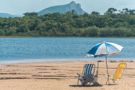Beach umbrella, two beach chairs in the sand near to a lake, a green forest is on the other margin of the lake and beyond it a mountain is standing at Paulo Cezar Vinha park, in Setiba, Espirito Santo Imagens - 129721345