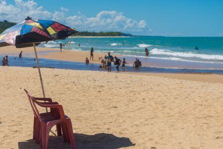 Ein roter Plastikstuhl unter einem Sonnenschirm mit Mustern an einem belebten Strand von Trancoso, Porto Seguro, Bahia, mit Touristen, die bei der Begegnung der Mangroven mit dem Meer schwimmen?
