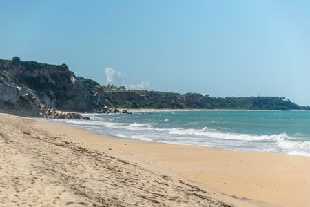 Vertical panorama of the seacoast of the personless Taipe beach, with brown seaweed in the harsh sand, a blue ocean and natural cliffs formed by rock exposures at Trancoso, Porto Seguro, Bahia