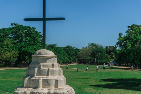 Catholic monument of a church of Quadrado of Trancoso in focus, a concrete structure painted in white, a wooden cross over it, and kids playing soccer in a grass field at Trancoso, Porto Seguro, Bahia
