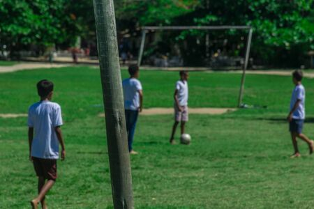 Small local boys dressed in white and playing soccer in a grass field with a simple netless goal near some houses in a village of Quadrado of Trancoso, at Porto Seguro, Bahia, a tourism landmark