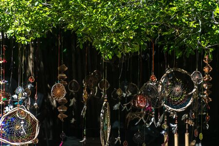 Dark outdoor view of a lot of hippie and colorful dream catchers with feather decorations and intricate patterns hanging onto tree branches of a tropical beach.