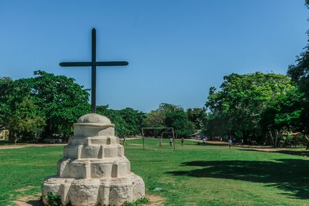 Circular concrete shrine painted in white at Trancoso, Porto Seguro, with a cross over it, in front of a grass field with many trees on the borders and children playing with a ball in the back