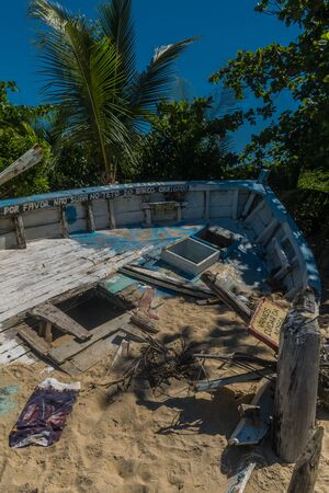 Abandoned and broken wooden blue boat berthed in the beach with a lot of sand, signs and dead plants over it, holes on the deck and a background of palm trees at Trancoso, Porto Seguro Imagens