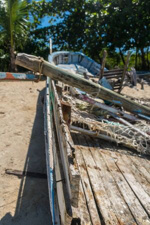 Perspective from the sides of an abandoned and blue wooden boat hanging in the beach sand with a heavy mast fallen over it, some fishnets inside and a background of trees at Trancoso, Porto Seguro
