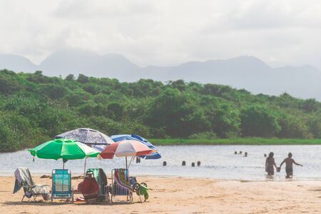 Five umbrellas are stuck in the sand, some people are having a swim in the lake with only their head of of water, one margin has a forest at Paulo Cezar Vinha park, in Setiba, Espirito Santo