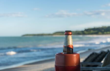 Closeup and detailed view of the upper part of a beer bottle with a red and white aluminium label, in front of a paradisiac view of a tropical beach bay with ocean waves.
