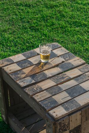 A checkered wood box is being used as a table, on its surface there is a cup full of beer and its shadow, the table is placed on a grass field, the grass is well cut and very green