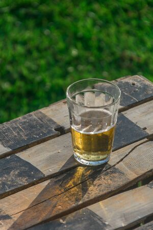 A tradicional brazilian glass called american cup full of pale beer with foam on its surface, the glass is placed on a checkered rustic wood table that finds itself on a green grass field Imagens