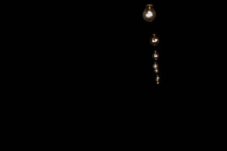 Dark and profound overview of a sequence of aligned incandescent light bulbs forming a line and hanging into the air going inwards into the shadows at the right corner of the picture