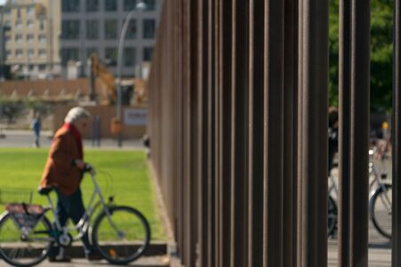 Elder berliner cyclist woman dressed in a brown coat near a grass field looking at the metal bars of the Memorial of the Berlin Wall at the Memorial Park in Germany, during the daylight