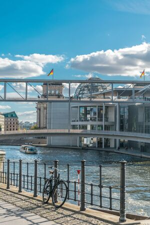 Scenic view of a bicycle leaning in a metal fence, with a boat riding in the Spree river and the metal architecture of the german parliament with national flags on its roof in the background