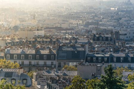 Overview of the endless buildings in the urban environment of Paris, France, at the Montmartre district during the sunrise, with a focus in an antique wide building with patterned windows