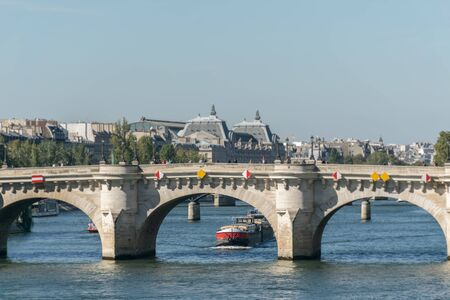 Overview of the architecture of a white bridge with yellow and red decorations over the Seine river in Paris with transportation boats passing by and an urban environment with trees in the background