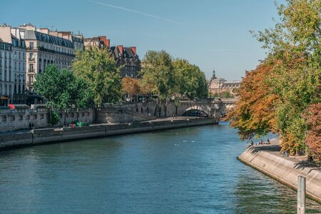 Perspective of the natural Seine river among the urban environment of Paris, France, with voluptuous trees and people relaxing at the margins near classical buildings during the day