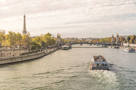 Busy and sunny day in Paris, France with a transportation boat full of tourists riding over the Seine river with the eiffel tower in the left and the Alexander III bridge in the background Zdjęcie Seryjne