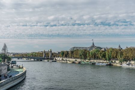 Distinct overview of the sunlight reflections over the Seine river, near the Alexander III bridge and the Grand Palais with many boats, numerous aligned trees and clouds in a blue sky