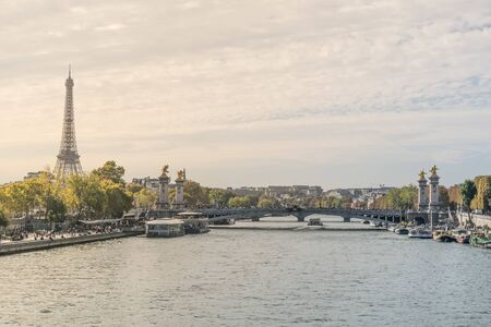 Beautiful postcard view of the Seine river crossing the Paris city in France, with tourist attraction boats in the margins at the eiffel tower and the Alexander III bridge in the background