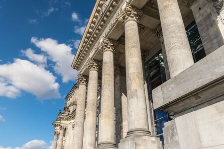 Upwards perspective of the architecture of the great classical columns of the facade of the German parliament in Berlin, Germany, during a sunny day Imagens