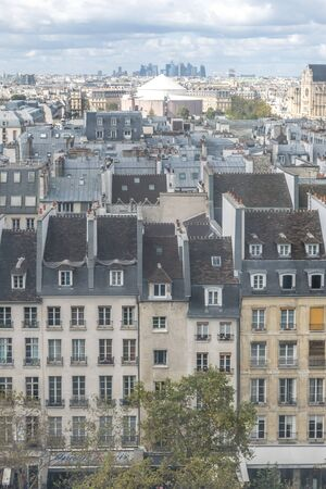 View of the patterns of the symmetrical and classical apartment windows, a portrait of the architecture of the modern Paris city, in France, with trees on the street and many buildings in the skyline