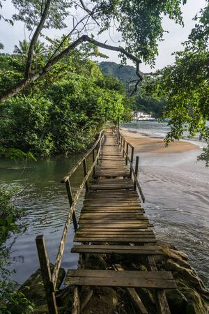 Calm and in depth view of natural landscape during the daylight, with focus on a broken wooden bridge crossing a clear river flowing into the sea, with trees and mountains in the background Imagens